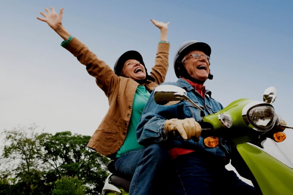 happy retired couple on a motorcycle